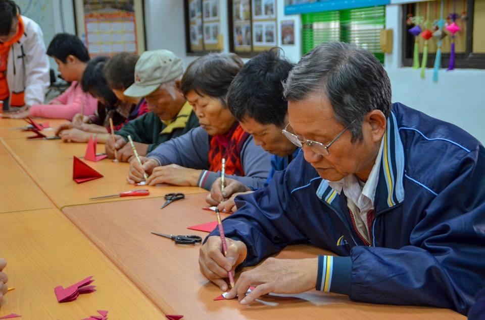 剪紙藝術課有許多長輩參與,爺爺奶奶們一起耐心專注地畫圖、剪紙.jpg