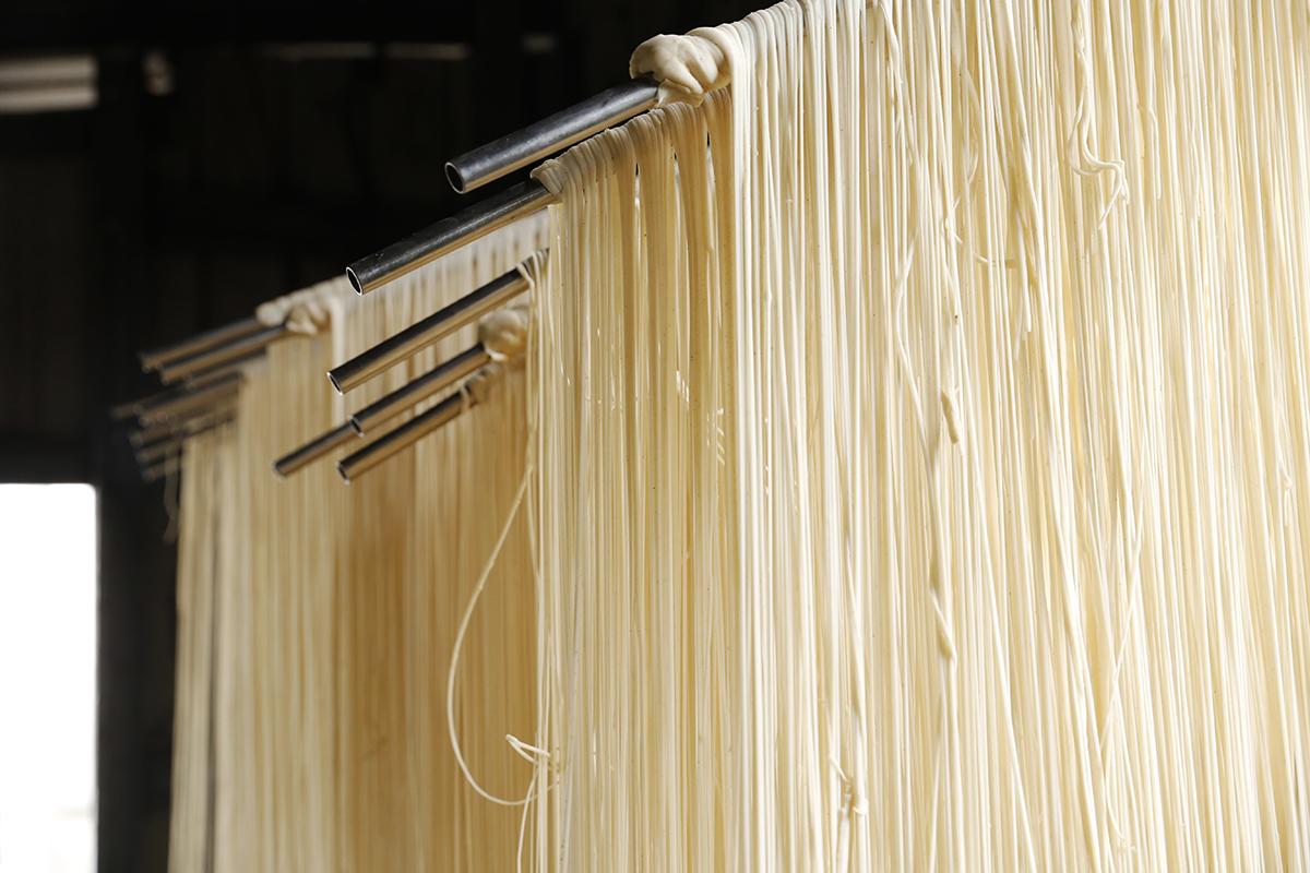 「手展麵線」我們找到了三峽在地麵線職人,憑著將近四十年的純手工,製作可以入湯的「麵線」,吃起來特別Q彈潤口,每日工時近十三個鐘頭,麵粉發酵,拉甩四至五次,接著進行達五十多度高溫的烘乾作業,經過繁複的過程而呈現的工藝美味,是機器製麵無可取代的好味道。 | 禾乃川國產豆製所 | 改變生命的豆漿店