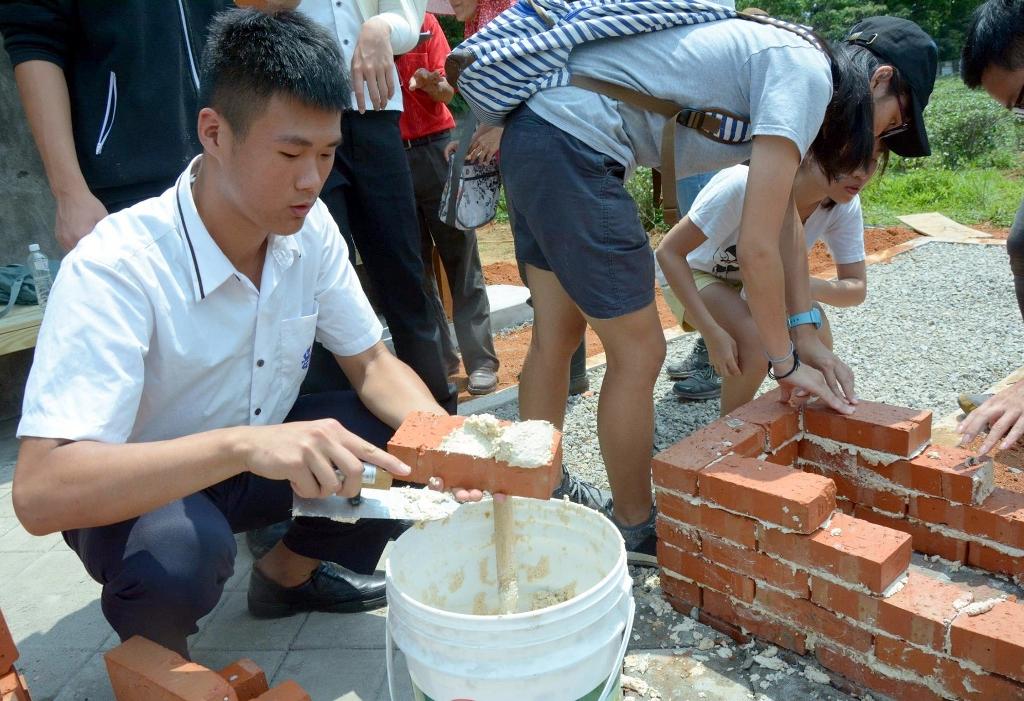 通稿照片05-高中生及大學生參與佳安里社區工作坊,興奮地蹲在地上體驗古早砌磚工法.jpg