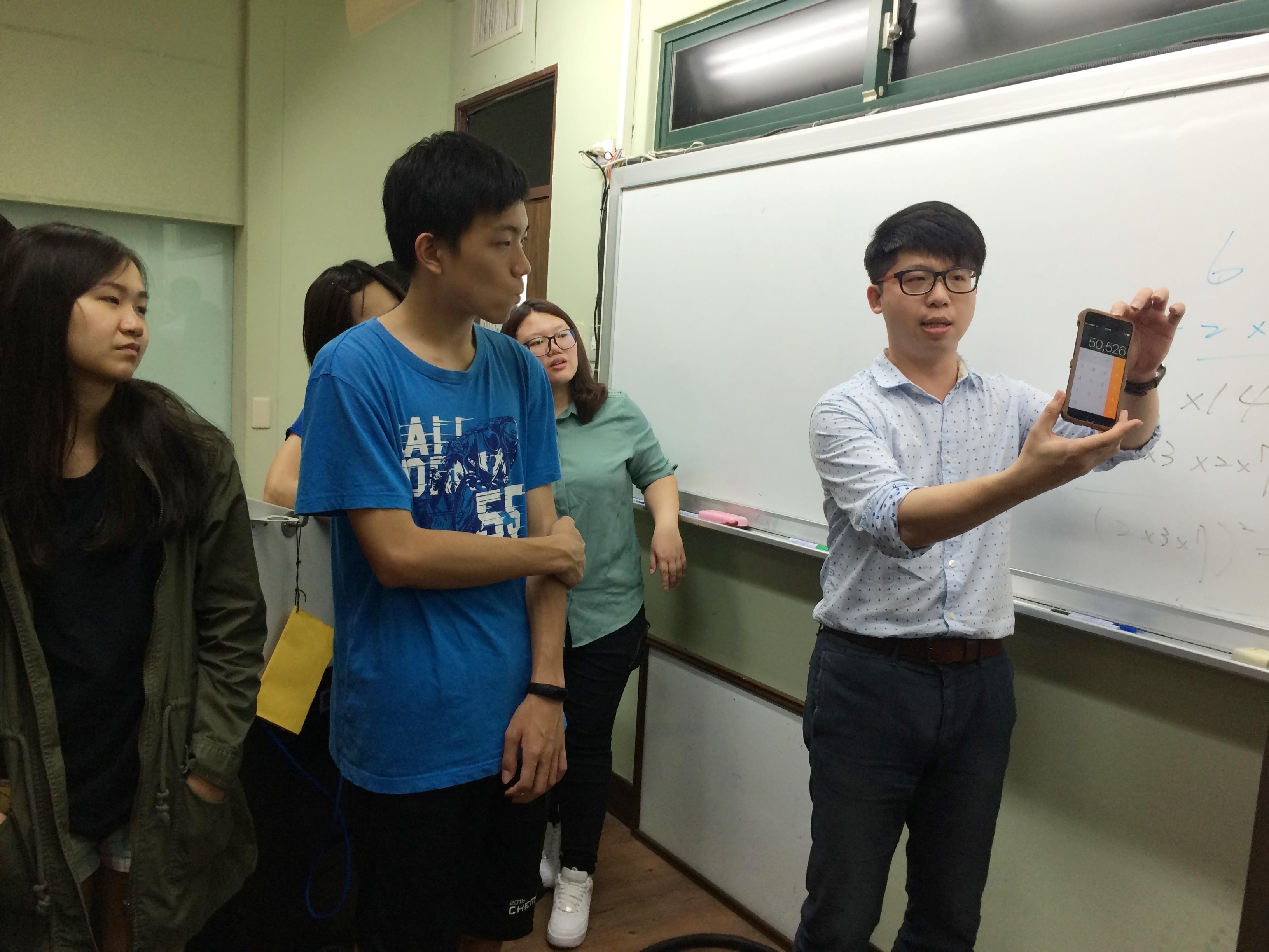 通稿照片3-莊惟棟老師(右一)說明手機計算機預言魔術,是應用質因數分解概念。.JPG