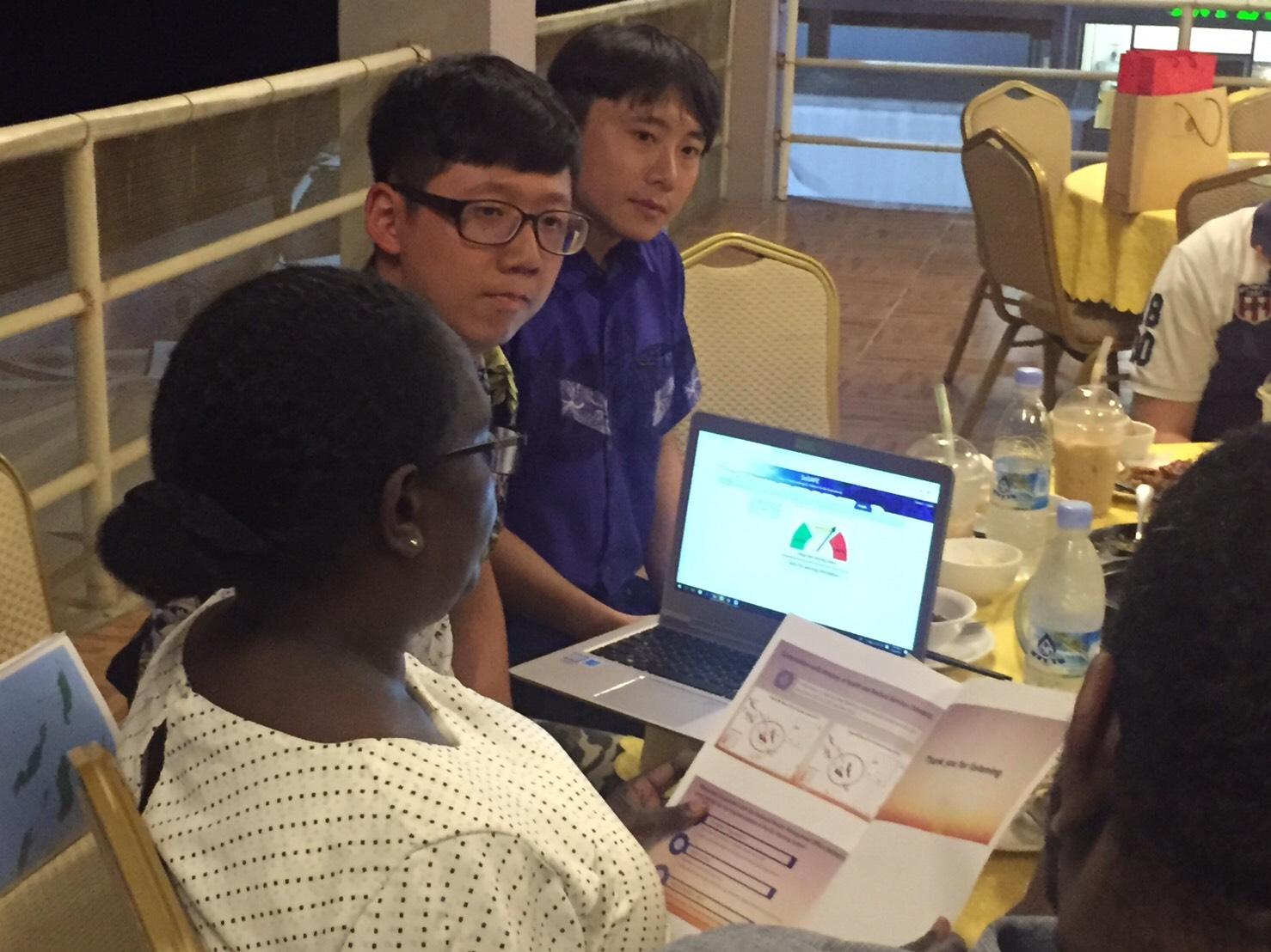中原大學環工系學生林昱翰(左二)向索國官員解說類登革熱預警系統的建置構想。.jpg